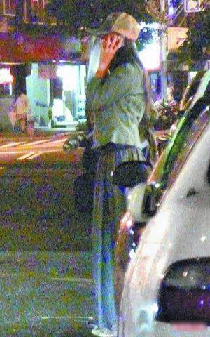 林志玲压低帽子在街边讲电话。
