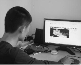 孩子父亲涂建文在电脑上翻看两个女儿生前的生活照。